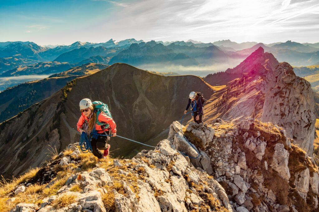 2 men hiking on mountain during daytime